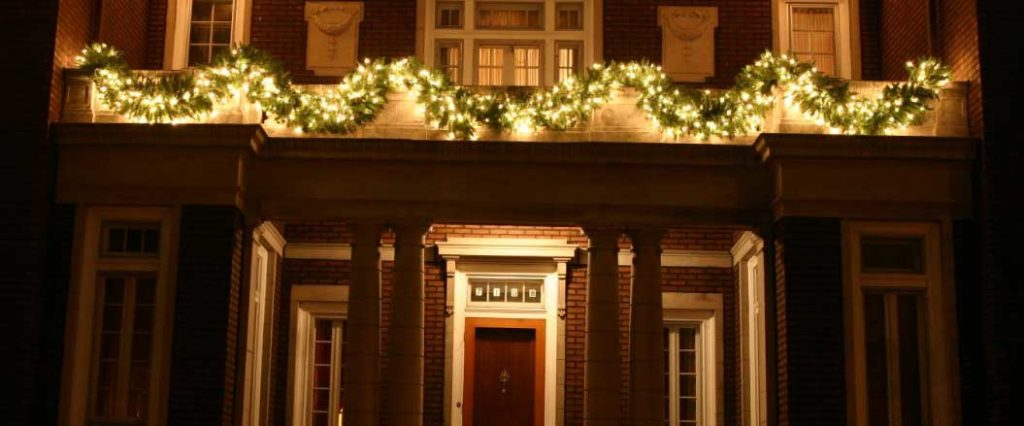 holiday garland draping from second story balcony above front door