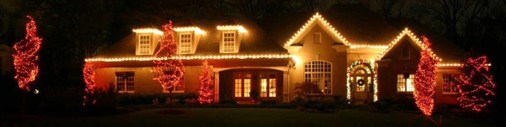 holiday lighting along gutter of house with red mini lights in trees and garland around front door